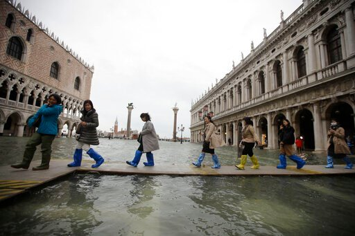 (AP Photo/Luca Bruno). People use trestle bridges to walk in a flooded St. Mark's Square at Venice, Friday, Nov. 15, 2019.The high-water mark hit 187 centimeters (74 inches) late Tuesday, Nov. 12, 2019, meaning more than 85% of the city was flooded. Th...