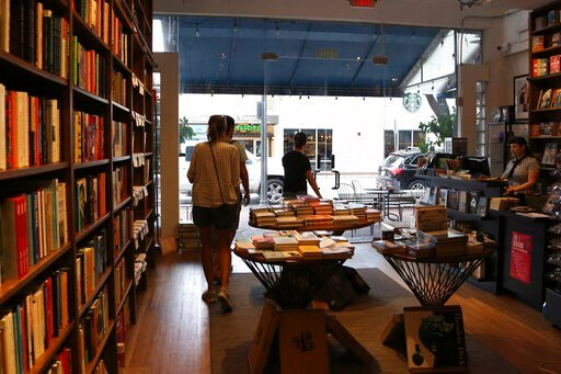 (AP Photo/Lynne Sladky). In this Nov. 6, 2019, photo, people shop at Books & Books, a locally owned business, in the Coconut Grove neighborhood in Miami. On Friday, Nov. 15, the Commerce Department releases U.S. retail sales data for October.