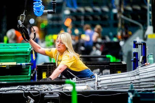 (Jake May/The Flint Journal via AP, File). FILE - In this June 12, 2019, file photo General Motors employees work on the chassis line as they build the frame, power train and suspension onto the truck's body at the Flint Assembly Plant in Flint, Mich. ...