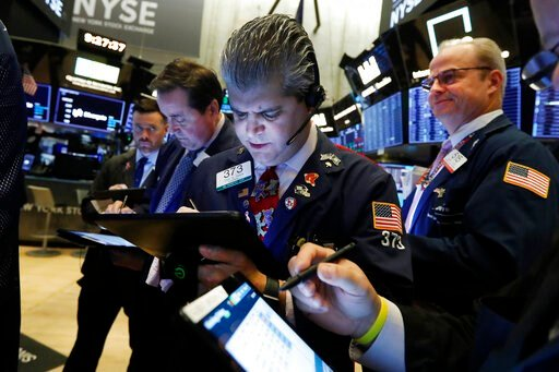 (AP Photo/Richard Drew, File). FILE - In this Nov. 7, 2019, file photo John Panin, center, works with fellow traders on the floor of the New York Stock Exchange. The U.S. stock market opens at 9:30 a.m. EST on Friday, Nov 15.