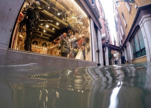 (AP Photo/Luca Bruno). A man holds up a phone during a video call to show a a flooded alley outside a shop, in Venice, Italy, Friday, Nov. 15, 2019. Exceptionally high tidal waters returned to Venice on Friday, prompting the mayor to close the iconic S...