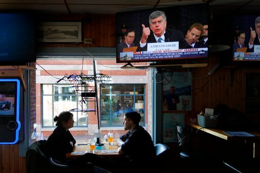 (AP Photo/Robert F. Bukaty). Olivia Tobin and her fiancé, Jordan Ashby, ignore the televised impeachment hearings playing on monitors at the Commercial Street Pub, Wednesday, Nov. 13, 2019, in Portland, Maine. Tobin is an Irish citizen who has a green ...