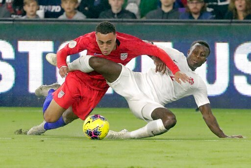 (AP Photo/John Raoux). U.S. defender Sergino Dest, left, gets tangled up with Canada defender Richie Laryea while going after the ball during the first half of a CONCACAF Nations League soccer match Friday, Nov. 15, 2019, in Orlando, Fla.