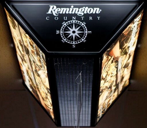 (AP Photo/Keith Srakocic, File). FILE - In this March 1, 2018 file photo, a light advertising Remington products hangs from the ceiling at Duke's Sport Shop in New Castle, Pa. For years, the gun industry has been immune from most lawsuits, but a recent...