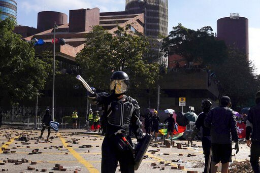(AP Photo/Vincent Yu). A protestor wearing a helmet and body armor gestures during unrest near Hong Kong Polytechnic University in Hong Kong, Sunday, Nov. 17, 2019. Police have fired tear gas at protesters holding out at Hong Kong Polytechnic Universit...