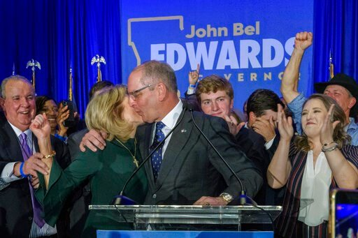 (AP Photo/Matthew Hinton). Louisiana Gov. John Bel Edwards celebrates with his wife Donna Edwards as he arrives to address supporters at his election night watch party in Baton Rouge, La., Saturday, Nov. 16, 2019.