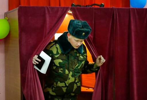 (AP Photo/Sergei Grits). A Belarus' Army serviceman casts his ballot at a polling station during parliamentary elections, in Minsk, Belarus, Sunday, Nov. 17, 2019.