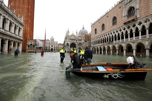 (AP Photo/Luca Bruno). A man sits on a small boat in a flooded St.Mark square in Venice, Italy, Sunday, Nov. 17, 2019. Venetians are bracing for the prospect of another exceptional tide in a season that is setting new records. Officials are forecasting...