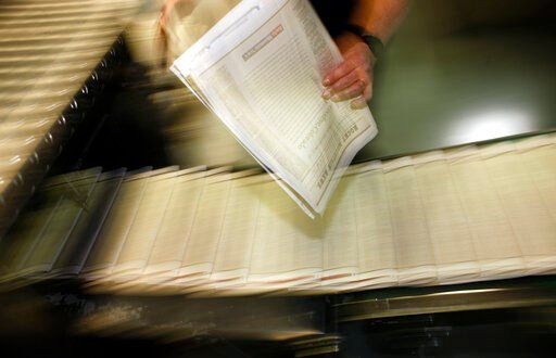 (AP Photo/David Zalubowski, File). FILE - In this Feb. 26, 2009 file photo, a pressman pulls a copy of one of the final editions of the Rocky Mountain News off the press in the Washington Street Printing Plant of the Denver Newspaper Agency in Denver. ...