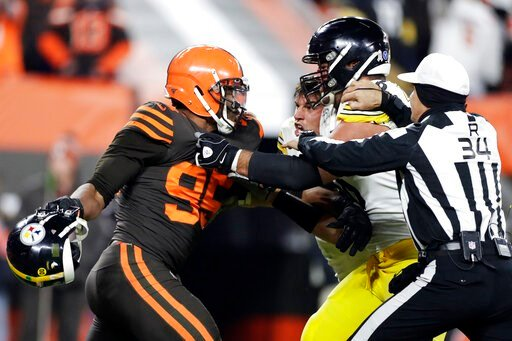 (AP Photo/Ron Schwane). Cleveland Browns defensive end Myles Garrett, left, gets ready to hit Pittsburgh Steelers quarterback Mason Rudolph, second from left, with a helmet during the second half of an NFL football game, Thursday, Nov. 14, 2019, in Cle...