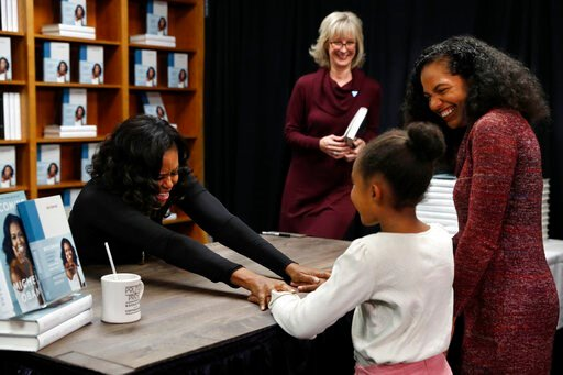 (AP Photo/Jacquelyn Martin). Former first lady Michelle Obama holds hands with Kaitlyn Saunders, 8, next to her mother Katrice Saunders, of Washington, after the 8-year-old told Obama how inspired she is by her and how she is a competitive figure skate...