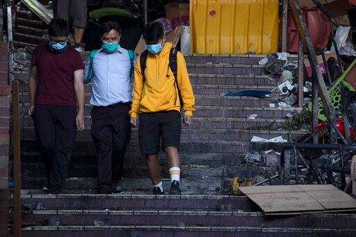 (AP Photo/Ng Han Guan). A school principal, center, escorts two youths to surrender to the police at the Hong Kong Polytechnic University in Hong Kong on Tuesday, Nov. 19, 2019. Police tightened their siege of the university campus where hundreds of pr...