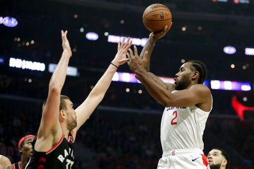 (AP Photo/Chris Carlson). Los Angeles Clippers forward Kawhi Leonard, right, shoots over Toronto Raptors center Marc Gasol during the second half of an NBA basketball game in Los Angeles, Monday, Nov. 11, 2019.