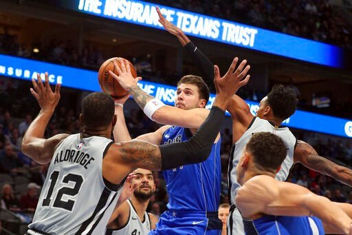 (AP Photo/Richard W. Rodriguez). Dallas Mavericks forward Luka Doncic (77) puts up a shot against San Antonio Spurs center LaMarcus Aldridge (12) and San Antonio Spurs guard Dejounte Murray (5) in the first half of an NBA basketball game Monday, Nov. 1...