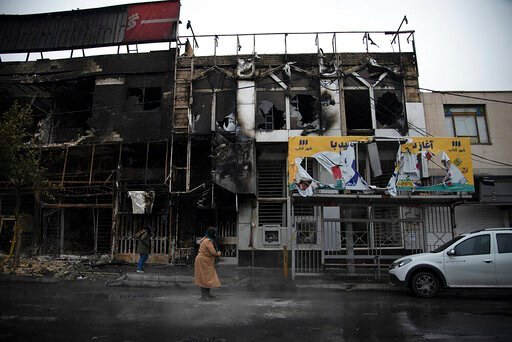 (Masoume Aliakbar/ISNA via AP). In this photo taken Monday, Nov. 18, 2019, and released by Iranian Students' News Agency, ISNA, people walk past buildings which burned during protests that followed the authorities' decision to raise gasoline prices, in...