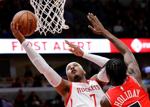 (AP Photo/Nam Y. Huh, File). FILE - In this Nov. 3, 2018, file photo, Houston Rockets forward Carmelo Anthony, left, drives to the basket against Chicago Bulls forward Justin Holiday during the first half of an NBA basketball game in Chicago. A person ...