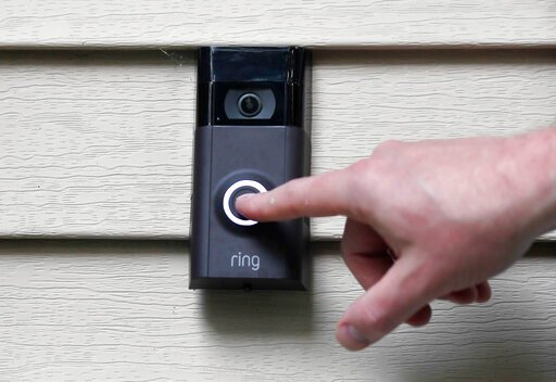 (AP Photo/Jessica Hill, File). FILE - In this July 16, 2019, file photo, Ernie Field pushes the doorbell on his Ring doorbell camera at his home in Wolcott, Conn. Amazon says it has considered adding facial recognition technology to its Ring doorbell c...