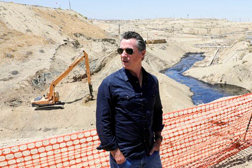 (Irfan Khan/Los Angeles Times via AP, Pool, File). FILE - In this July 24, 2019, file photo, Gov. Gavin Newsom tours the Chevron oil field west of Bakersfield where a spill of more than 800,000 gallons flowed into a dry creek bed in McKittrick, Calif. ...