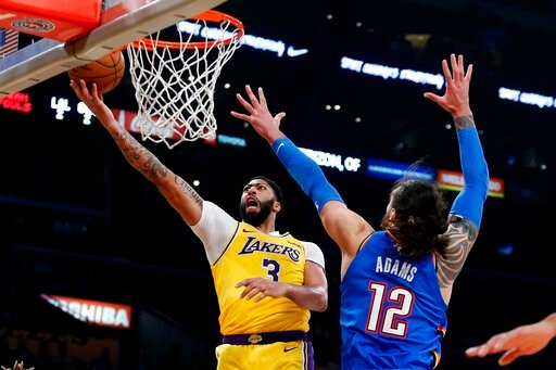 (AP Photo/Ringo H.W. Chiu). Los Angeles Lakers' Anthony Davis (3) goes to the basket as Oklahoma City Thunder's Steven Adams (12) dfends during the first half of an NBA basketball game Tuesday, Nov. 19, 2019, in Los Angeles.