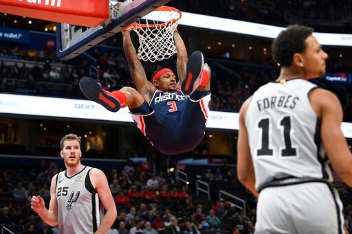 (AP Photo/Nick Wass). Washington Wizards guard Bradley Beal (3) hangs from the rim after his dunk between San Antonio Spurs center Jakob Poeltl (25) and guard Bryn Forbes (11) during the first half of an NBA basketball game Wednesday, Nov. 20, 2019, in...