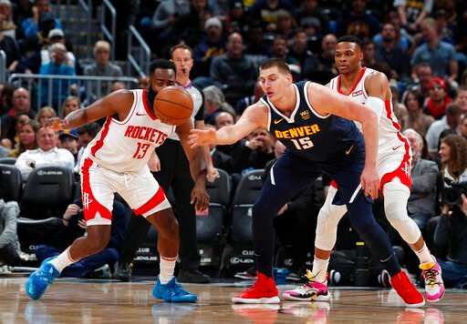(AP Photo/David Zalubowski). Houston Rockets guard James Harden, left, pursues a loose ball with Denver Nuggets center Nikola Jokic in the first half of an NBA basketball game Wednesday, Nov. 20, 2019, in Denver.