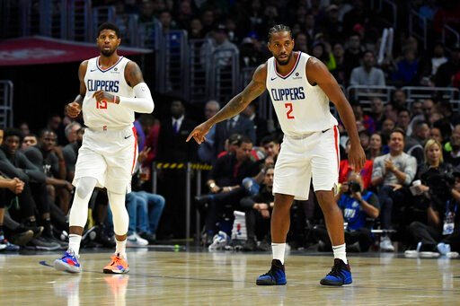 (AP Photo/Mark J. Terrill). Los Angeles Clippers forward Paul George, left, and forward Kawhi Leonard stand on the court during the second half of the team's NBA basketball game against the Boston Celtics on Wednesday, Nov. 20, 2019, in Los Angeles.