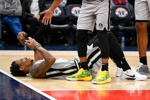 (AP Photo/Nick Wass). San Antonio Spurs guard DeMar DeRozan lies on the court after he was fouled during the second half of the team's NBA basketball game against the Washington Wizards, Wednesday, Nov. 20, 2019, in Washington. The Wizards won 138-132.