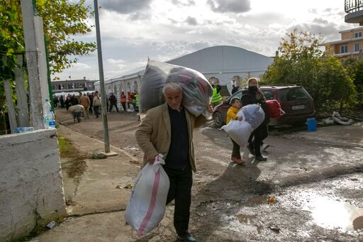 (AP Photo/Visar Kryeziu). People carry clothes and other supplies distributed by authorities in Thumane, western Albania, Friday, Nov. 29, 2019. The operation to find survivors and recover bodies from Albania's deadly earthquake was winding down Friday...