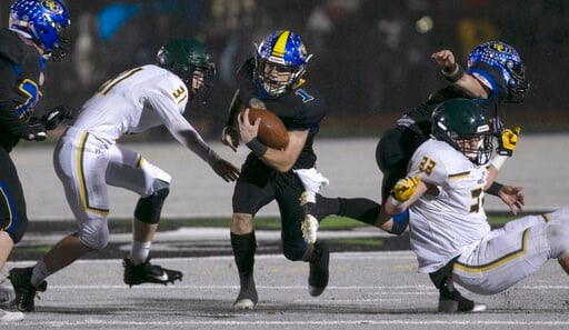 (AP Photo/Rich Pedroncelli). Sutter Union's Cory McIntyre, center, runs past Paradise's Josh Alvies, left, and Ashton Wagner, right, during the first quarter of a Northern Section Division III high school football playoff game in Yuba City, Calif., Sat...