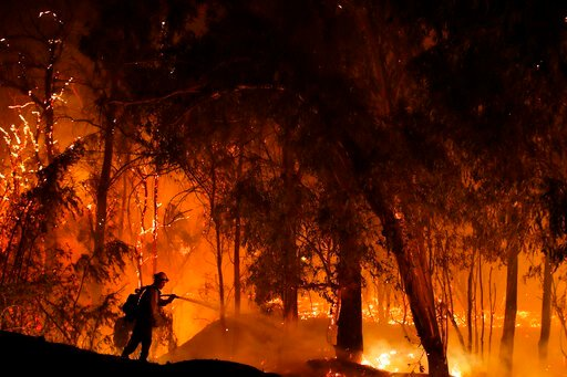 (AP Photo/Marcio Jose Sanchez, Fire). FILE - In this Oct. 31, 2019, file photo, a firefighter battles a wildfire known as the Maria Fire in Somis, Calif. A new technology being tested by California utilities, such as Pacific Gas & Electric Co. and ...