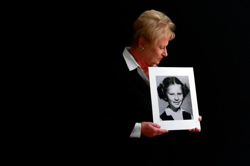 (AP Photo/Gregory Bull). In this Nov. 20, 2019, photo, Nancy Holling-Lonnecker, 71, poses with a picture taken of her as a young girl, at her home in San Diego. Holling-Lonnecker plans to take advantage of an upcoming three-year window in California th...