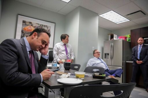 (AP Photo/Bebeto Matthews). In this Tuesday, Oct. 29, 2019, photo, attorney Adam Slater, left, checks his phone during a working lunch with lawyers in his firm including partner Jonathan Schulman, second from left, Steven Alter, second from right, and ...