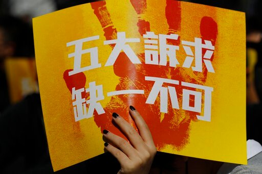 "(AP Photo/Vincent Thian). A pro-democracy supporter holds up a card which reads ""Five Demands, Not one less"" during a rally by the advertising industry in Hong Kong on Monday, Dec. 2, 2019. Thousands of people took to Hong Kong's streets Sunday in a ne..."