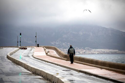(AP Photo/Daniel Cole). A man walks along the coast as clouds form over Marseille, France, Sunday, Dec. 1, 2019. The southern France region is under alert for heavy rain and floods.
