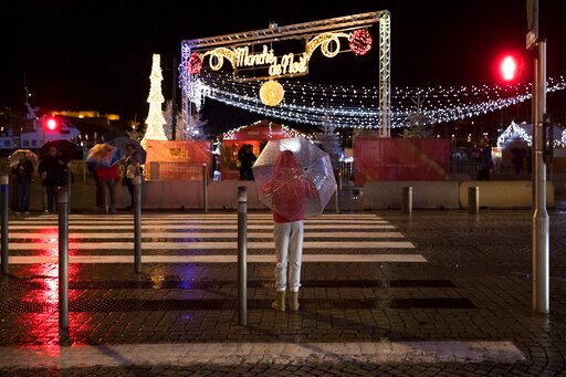 (AP Photo/Daniel Cole). A pedestrian waits with an umbrella to cross the road during a storm in Marseille, Sunday, Dec. 1, 2019. The southern France region is under a red alert for heavy rain and floods.