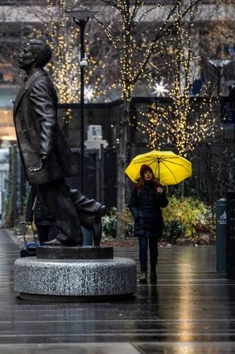 (Jose F. Moreno/The Philadelphia Inquirer via AP). An unidentified woman shields from the rain with an umbrella as she walks near the Octavius Catto statue, Sunday, Dec. 1, 2019 in Philadelphia.
