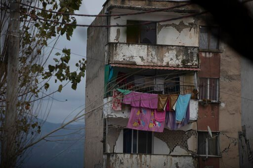 (AP Photo/Petros Giannakouris). In this Wednesday, Nov. 27, 2019 photo, laundry hangs on a line from a damaged building in Thumane, western Albania following a deadly earthquake. A handbag dangles from a coat-hanger, gleaming saucepans sit stacked in a...
