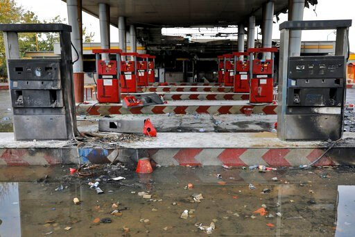 (AP Photo/Ebrahim Noroozi, File). FILE - In this Nov. 20, 2019, file photo, rainwater pools at a gas station attacked during protests over government-set gasoline prices in Tehran, Iran. Amnesty International says at least 208 people in Iran have been ...