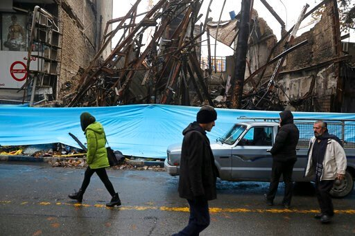 (AP Photo/Vahid Salemi, File). FILE - In this Nov. 20, 2019, file photo, people walk past buildings that were burned during recent protests, in Shahriar, Iran, some 40 kilometers (25 miles) southwest of the capital, Tehran. Amnesty International says a...