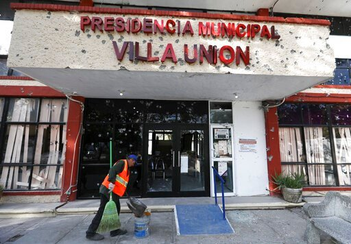 (AP Photo/Eduardo Verdugo). A worker cleans up outside City Hall, riddled with bullet holes, in Villa Union, Mexico, Monday, Dec. 2, 2019. The small town near the U.S.-Mexico border began cleaning up Monday even as fear persisted after 22 people were k...
