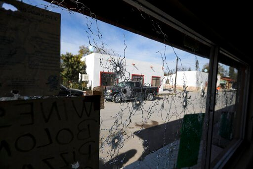 (AP Photo/Eduardo Verdugo). A shop's windows are riddled with bullet holes near City Hall after a gunbattle in Villa Union, Mexico, Monday, Dec. 2, 2019. The small town near the U.S.-Mexico border began cleaning up Monday even as fear persisted after 2...