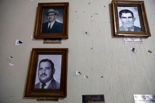 (AP Photo/Eduardo Verdugo). Portraits of former mayors of Villa Union hang on a wall riddled with bullet holes after a gunbattle, inside City Hall, in Villa Union, Mexico, Monday, Dec. 2, 2019. The small town near the U.S.-Mexico border began cleaning ...