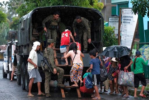(AP Photo). Residents ride a military truck as they evacuate to safer grounds in preparation for the coming of Typhoon Kammuri in Legazpi, Albay province, southeast of Manila, Philippines on Monday Dec. 2, 2109. The Philippines' main island, including ...