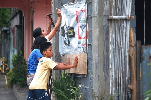 (AP Photo). Residents reinforce their house as they prepare for a coming typhoon in Legazpi, Albay province, southeast of Manila, Philippines on Monday Dec. 2, 2109. The Philippines' main island, including the national capital, Manila, is under a tropi...