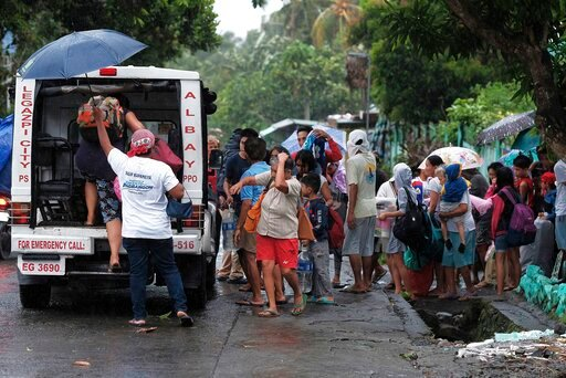 (AP Photo). Residents evacuate their area in preparation for the coming of Typhoon Kammuri in Legazpi, Albay province, southeast of Manila, Philippines on Monday Dec. 2, 2109. The Philippines' main island, including the national capital, Manila, is und...