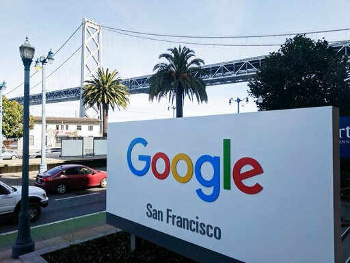 (AP Photo/Michael Liedtke, File). FILE - In this Oct. 31, 2018, file photo shows signage outside the offices of Google in San Francisco with the San Francisco-Oakland Bay Bridge in the background. Four workers fired from Google in November 2019 are pla...