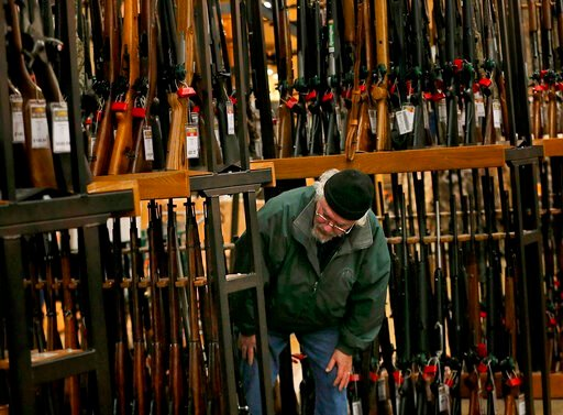 (Christian Gooden/St. Louis Post-Dispatch via AP). FILE - In this Nov. 29, 2019, file photo, a man looks at the shotgun section of Cabela's while shopping on Black Friday in Hazelwood, Mo. The number of background checks conducted by federal authoritie...