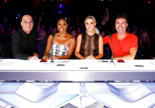 "(Trae Patton/NBC via AP). This image released by NBC shows celebrity judges, from left, Howie Mandel, Gabrielle Union, Julianne Hough, Simon Cowell on the set of ""America's Got Talent,"" in Los Angeles. Union is thanking supporters for defending her ami..."