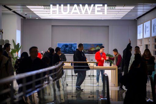 (AP Photo/Mark Schiefelbein). In this Nov. 20, 2019, photo, customers shop at a Huawei store at a shopping mall in Beijing. The founder of Huawei says the Chinese tech giant is moving its U.S. research center to Canada due to American restrictions on i...