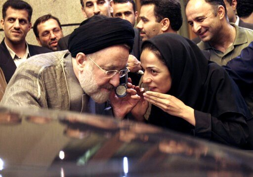 (AP Photo/Hasan Sarbakhshian, File). FILE - In this July 13, 2005, file photo, outgoing reformist Iranian President Mohammad Khatami talks on the phone with the mother of female journalist Masih Alinejad, right, after meeting with journalists in Tehran...